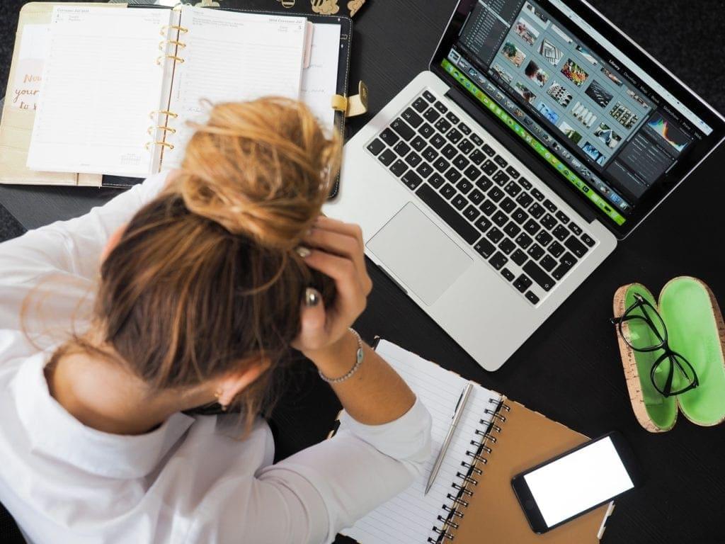 femme stressée de dos avec la tête dans ses mains devant un ordinateur