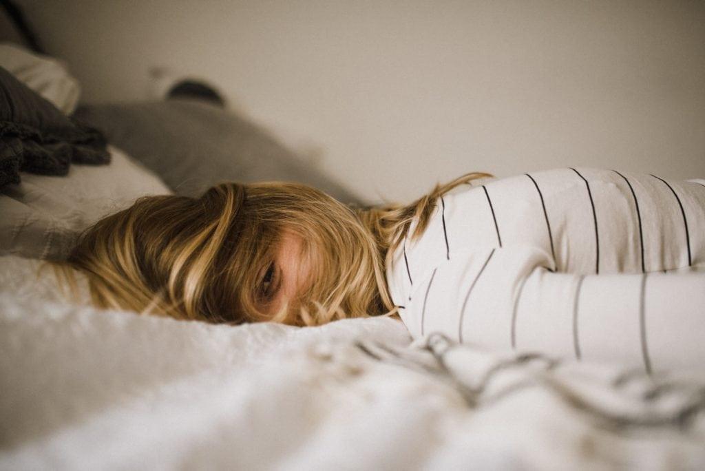 femme qui souffre d'insomnie couchée sur un lit blanc