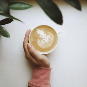 latte au maca tenu dans une main gauche