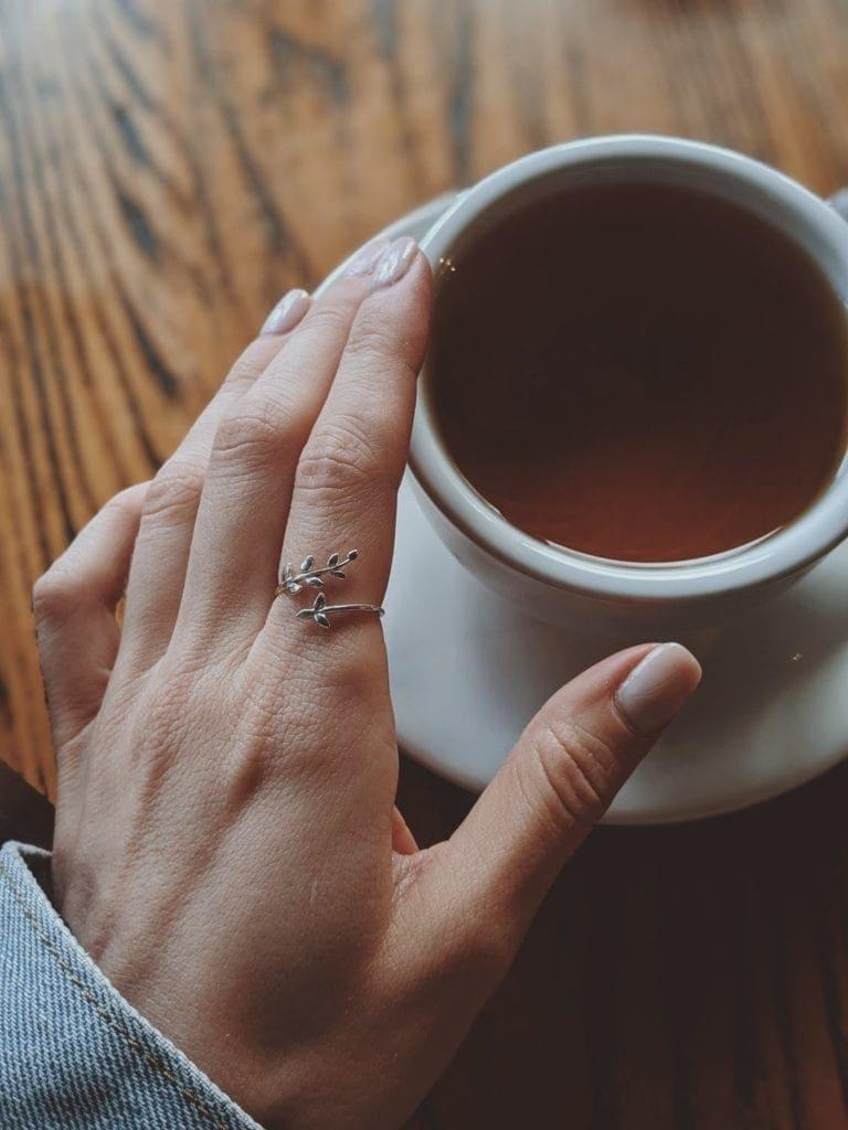 main qui tient une tasse de puerh